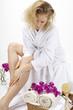 Wellness - Frau trägt Körperöl auf ihr Bein auf / Nahaufnahme