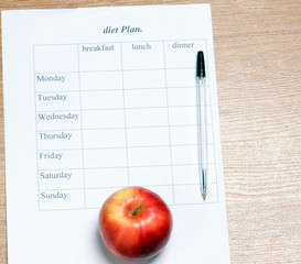 diet Plan. diet plan, pencil and apple lying on a wooden surface