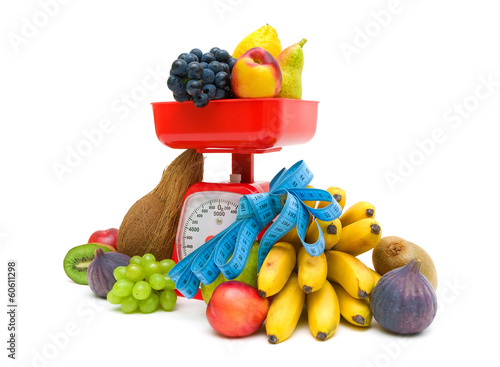 fruit, kitchen scale and measuring tape on a white background