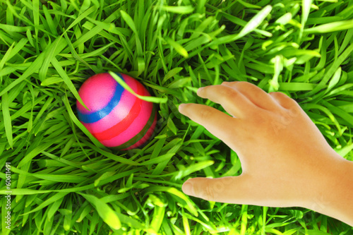Hand reaching for Easter egg on green grass