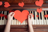 Child hands holds paper heart on a background of piano