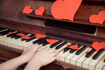 Child is playing on a piano on Valentine's Day