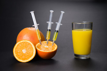 Orange with vitamins in the syringe