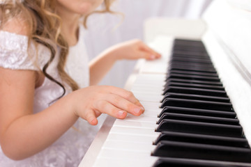 little girl  in white  dress playing on white piano, close-up