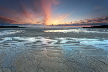 Rising tide on sandy beach at sunset