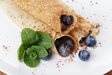homemade blinis or crepes with blueberries and jam