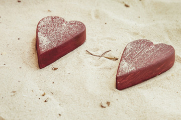 Two romantic red  hearts  on the sand