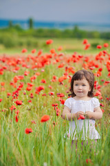 very happy child girl in poppy field