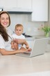 Smiling mother with baby using laptop