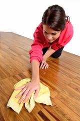 Ragazza che pulisce il pavimento di legno