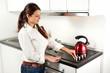 Ragazza in cucina che accende il fornello per il tè