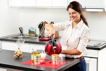 Ragazza che prepara il tè in cucina