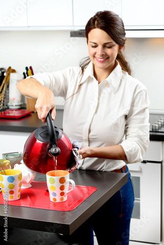 Ragazza  in cucina che versa il tè