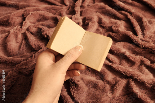 Woman holding a tiny book