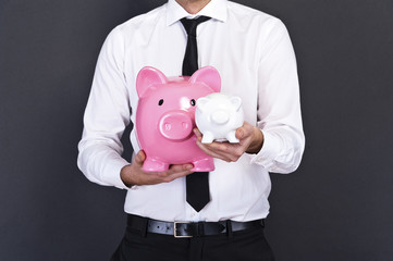 portrait of young man holding a two piggy bank against a grunge