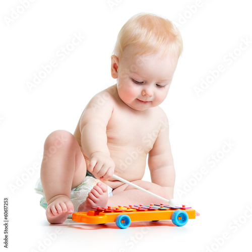 Funny child playing  with musical toys. Isolated on white backgr