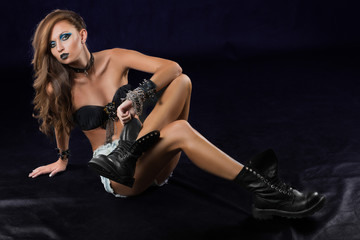 punk girl in heavy boots in bracelets and chains