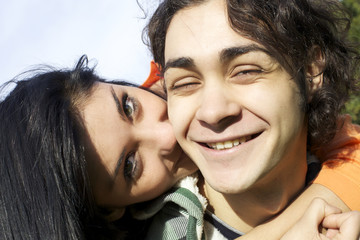 Happy young man being kissed by girlfriend
