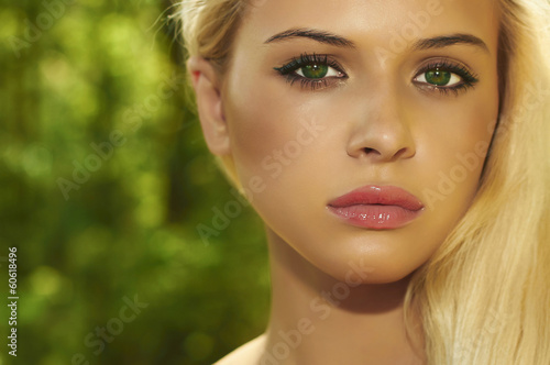 Beautiful Blond Woman in Forest.Summer Sunlight.Green eyes