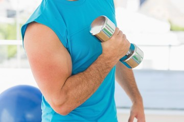 Mid section of a sporty man with dumbbell in gym