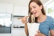 Smiling young woman eating noodles in kitchen