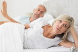 Woman ignoring mature man while lying in bed