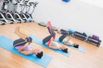 Sporty women with exercise bands in fitness studio