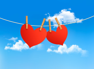 Two hearts hanging on a rope in front of a sky. Valentine's day