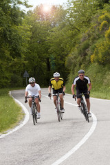 Three Cyclists racing on a hilly road