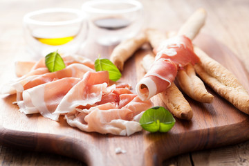 italian prosciutto ham grissini bread sticks olive oil
