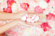womans cupped hands with flower petals