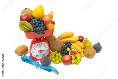 fruit, measuring tape and kitchen scales close up on white backg