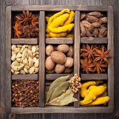 Assorted colorful spices in old wooden box