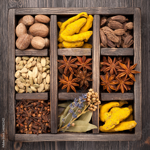 Assorted colorful spices in an old wooden box