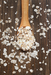oat flakes in wooden spoon on wood