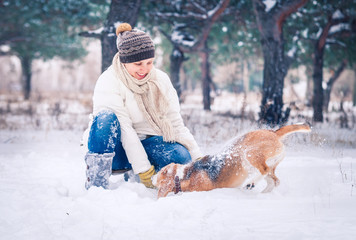 Happy woman playing with her pet in snow