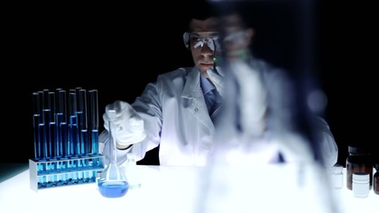 Young Scientist Examining Beaker in Laboratory Experiment Test