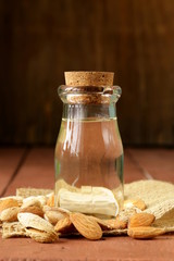 almond oil in a glass bottle with whole nuts