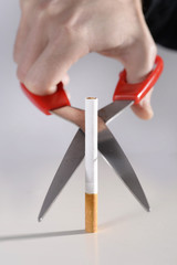 man cutting cigarette with scissors  representing quit smoking