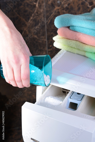 Female hands poured powder in washing machine close-up