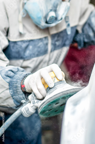 auto mechanic using the power buffer machine