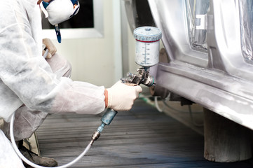auto worker spraying grey paint on a car in an auto garage