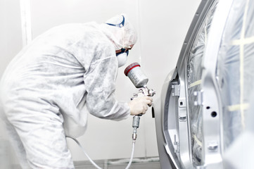 mechanical engineer working on painting a car in painting booth