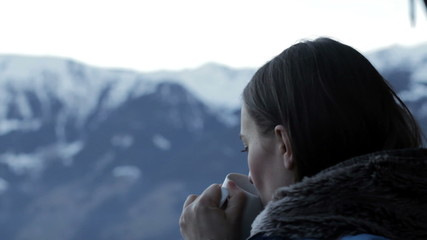 Beautiful girl drinking hot tea in the mountains, close up