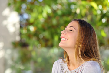 Young happy smiling woman doing deep breath exercises