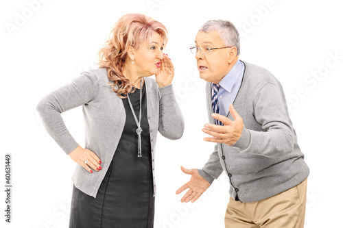 Mature lady whispering a secret to man