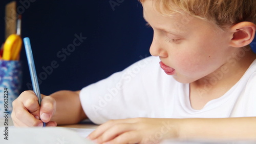 Little boy diligently writes his homework