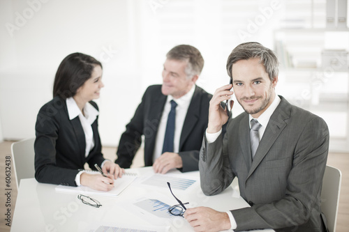 Businessman at phone in meeting - 60632438