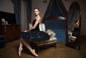 Ballerina in black tutu sitting in armchair in luxury interior