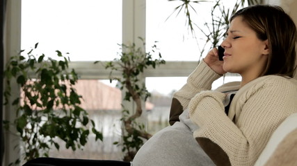 Nervous woman in pregnant talking on the phone